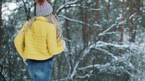 La mujer bastante joven en una chaqueta amarilla corre alrededor de un bosque del invierno metrajes