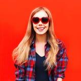 La mujer bastante joven feliz del retrato en gafas de sol rojas forma el corazón Imagen de archivo