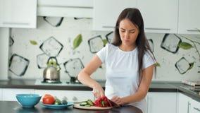 La mujer bastante joven prepara el almuerzo y destroza el pepino verde para la ensalada con el cuchillo afilado almacen de video