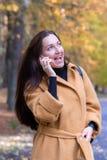 La mujer bastante joven que camina en Autumn Park Talking en caída móvil de las hojas del teléfono se relaja fotografía de archivo