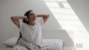 La mujer bastante joven se está sentando en dormitorio soleado por la mañana, estirando las manos para arriba almacen de metraje de vídeo
