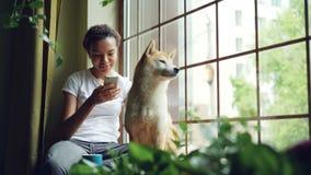 La mujer bastante joven se está sentando en travesaño de la ventana y está utilizando smartphone mientras que su perro tranquilo  almacen de metraje de vídeo