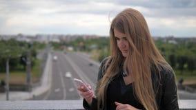 La mujer bastante joven utiliza un smartphone y endereza el pelo metrajes