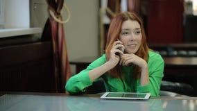 La mujer bastante joven utiliza una tableta, es distraída por una conversación telefónica agradable, sonriendo metrajes