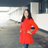La mujer bastante joven vistió una chaqueta roja al aire libre Fotografía de archivo