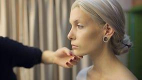 La mujer bastante rubia se prepara para la sesión fotográfica en vestuario metrajes