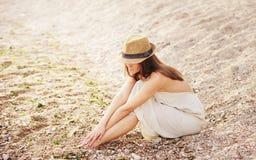 La mujer bastante tranquila relaja sentarse solamente en una playa de la arena foto de archivo libre de regalías