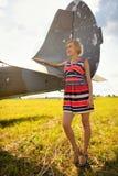 La mujer beautyful de la moda en vestido permanece cerca del viejo avión Fotografía de archivo libre de regalías