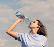 La mujer bebe el agua Fotos de archivo libres de regalías