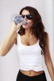 La mujer bebe el agua de la botella Fotografía de archivo libre de regalías
