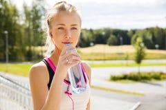 La mujer bebe el agua después de correr en el campo Fotos de archivo libres de regalías