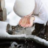 La mujer bebe el agua potable de sus manos Fotografía de archivo