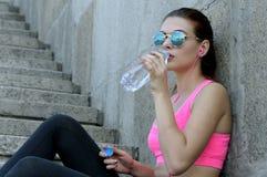 La mujer bebe el agua y escuchar la música Imágenes de archivo libres de regalías