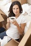 La mujer bebe el café que desempaqueta los rectángulos que mueven la casa Fotos de archivo libres de regalías