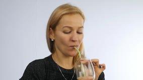 La mujer bebe el smoothie del detox, concepto sano de la forma de vida cóctel de la verdura y de la fruta Cámara lenta metrajes