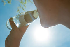 La mujer bebe una bebida efervescente en los rayos del sol que restauran en día caliente Fotos de archivo