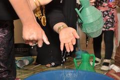 La mujer beduina lava las manos Imagen de archivo