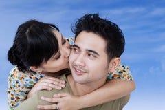 La mujer besa a su novio en el cielo azul fotografía de archivo