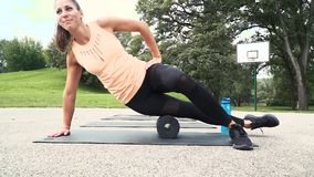 La mujer bien entrenada hermosa está haciendo ejercicios con el rollo de la faja almacen de video