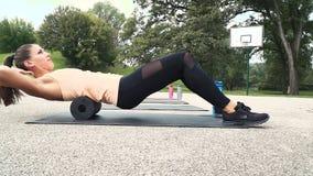 La mujer bien entrenada hermosa está haciendo ejercicios con el rollo de la faja almacen de metraje de vídeo