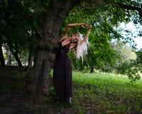 La mujer bien proporcionada joven se coloca debajo del árbol grande en parque de la ciudad Foto de archivo