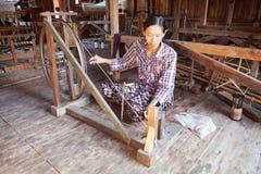 La mujer birmana es spinnig al hilo del loto Foto de archivo libre de regalías