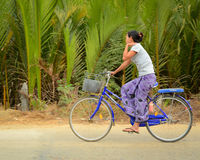 La mujer birmana monta la bicicleta a lo largo de la calle del campo Fotos de archivo