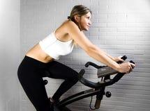 La mujer blanca monta la bici de ejercicio Foto de archivo libre de regalías