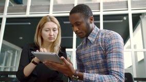 La mujer blanca y el hombre del afroamericano miran de cerca la tableta en las manos almacen de video
