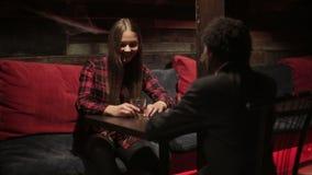 La mujer blanca y el hombre negro hacen diálogo en el restaurante Diversos amigos de la raza almacen de metraje de vídeo