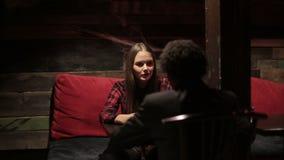 La mujer blanca y el hombre negro hacen diálogo en el restaurante Diversos amigos de la raza almacen de video