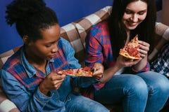 La mujer blanca y negra goza el comer de la pizza, primer imagen de archivo libre de regalías