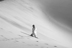 La mujer blanco y negro que se arrodilla en una duna del desierto fotografía de archivo