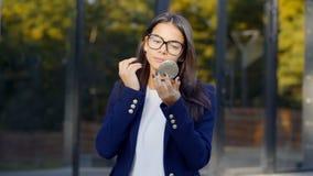 La mujer bonita acertada del estudiante que mira para duplicar y corrige su maquillaje con la barra de labios en fondo del edific metrajes