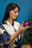 La mujer bonita adorna un árbol de navidad Imagen de archivo libre de regalías