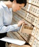 La mujer bonita busca algo en catálogo de tarjeta Imágenes de archivo libres de regalías