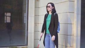 La mujer bonita ciega presenta un bastón en la calle almacen de metraje de vídeo