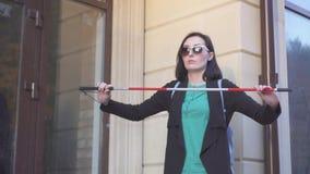 La mujer bonita ciega presenta un bastón en la calle, MES lento almacen de metraje de vídeo