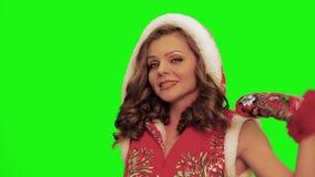 La mujer bonita con el traje y los guantes de la Navidad del pelo que llevan rizado y el timbrel en sus manos canta contra chroma almacen de metraje de vídeo