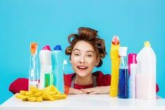 La mujer bonita con las herramientas de la limpieza sonríe en la cámara y parece contenta Foto de archivo libre de regalías