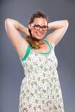 La mujer bonita con los vidrios que llevan del pelo marrón largo y la flor se visten Fotos de archivo libres de regalías