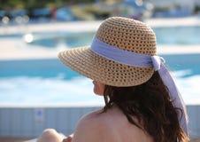 La mujer bonita con un sombrero de paja y ella grandes se relaja en el exclusi imagen de archivo