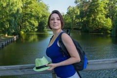 La mujer bonita con un sombrero y una mochila en el puente parquean Imagen de archivo