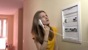 La mujer bonita consulta con el electricista en el teléfono del alambre cerca de la caja de disyuntor almacen de metraje de vídeo
