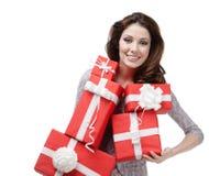 La mujer bonita da una gran cantidad de cajas de regalo Foto de archivo libre de regalías