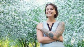 La mujer bonita de la chica joven está mirando la cámara y está sonriendo en bosque floreciente de la manzana con los flores blan metrajes