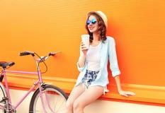 La mujer bonita de la moda bebe el café de la taza cerca de la bicicleta retra del rosa del vintage sobre naranja colorida fotografía de archivo