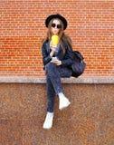 La mujer bonita de la moda bebe el jugo de la taza usando smartphone sobre ladrillos Imagen de archivo libre de regalías