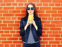 La mujer bonita de la moda en estilo negro de la roca bebe el zumo de fruta de la taza sobre fondo Imagenes de archivo