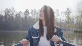 La mujer bonita del encanto en los pantalones y la chaqueta blancos a de los vaqueros se bate en el barco en el río, mirando alre almacen de metraje de vídeo